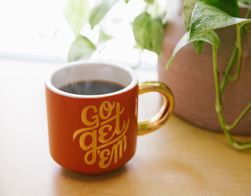 Red coffee mug with the words Go Get 'Em in front of a plant