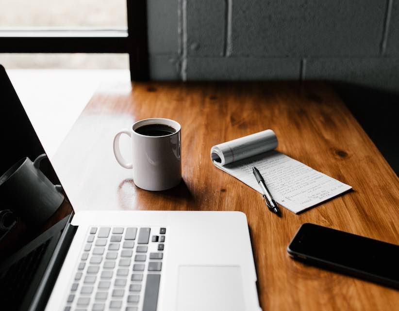 Image of a laptop, notebook, coffee cup, pen and cell phone on a wood desk
