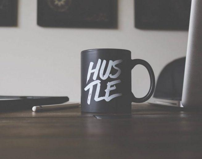 Black mug that says hustle on a computer desk